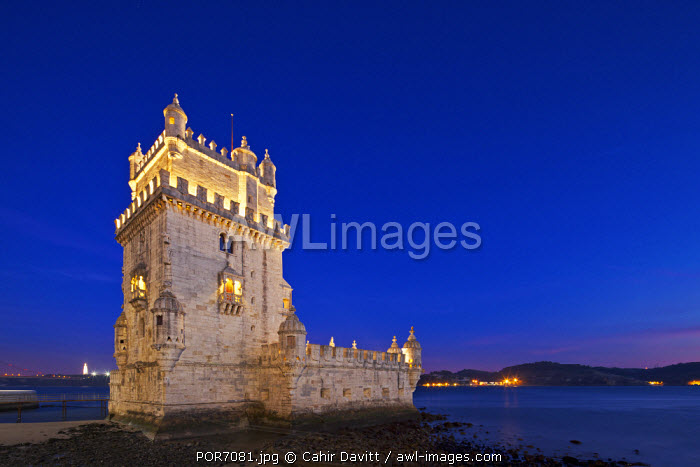 awl-images.com - Portugal / The early 16th century Portuguese Manueline Style, Torre de Belem designed by the architect Francisco de Arruda at twilight with the River Tagus Estuary in the background, in Pedroucos, Belem, Cruz Quebrada, Lisbon, Portugal.