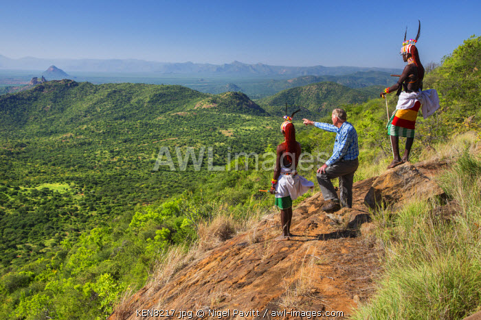 awl-images.com - Kenya / Kenya, Kirimun, Samburu County. Two Samburu warriors escort a tourist to a magnificent viewpoint on the edge of the Kirimun escarpment.