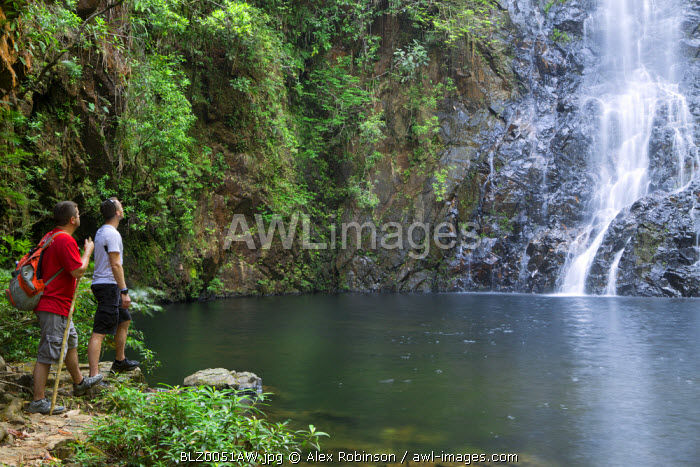 Central America, Belize, Mountain Pine Ridge, Hidden Valley, Butterfly Falls. Two tourists look out over a pool in front of the Butterfly falls (MR) (PR)