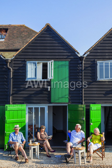 England, Kent, Whitstable, Couples Relaxing in front of Converted Fishermans Hut Accomodation