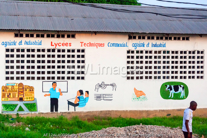 Africa, Congo, Point Noire. Man walking by hand painted sign on school.