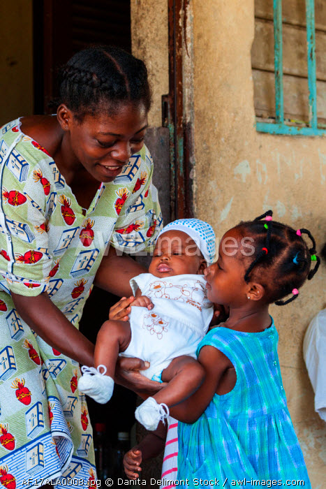 Africa, Gabon, Libreville. Mother handing baby to daughter to hold.