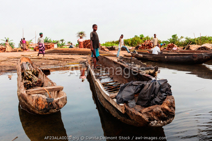 Africa, Liberia, Monrovia. People gathered by traditional pirogue boats on the Du River.