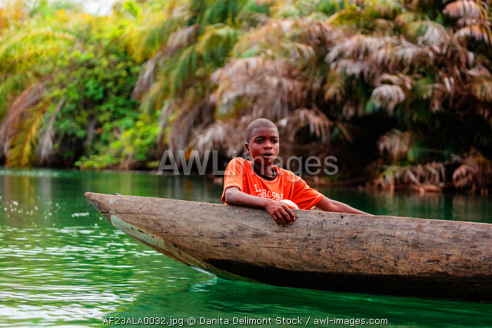 Africa, Liberia, Monrovia. Young boy in traditional pirogue moving down Du River.