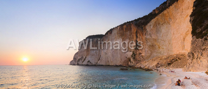 awl-images.com - Greece / Western Europe, Greece, Ionian Islands, Paxos. Tourists watching the sunset on Erimitis Beach.