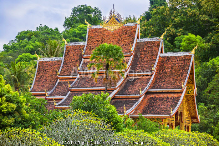 Laos, Luang Prabang, Luang Prabang Province. The sweeping roof of the fine temple in the grounds of the Haw Kham Royal Palace complex was built in the traditional style of Luang Prabang architecture.
