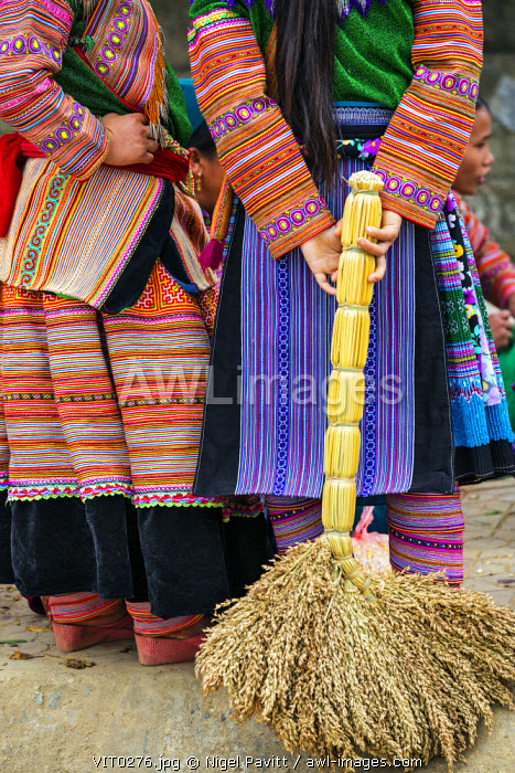 awl-images.com - Vietnam / Vietnam, Lao Cai Province, Bac Ha. Flower H�mong women in their colourful outfits and leggings pause at Bac Ha�s busy weekly Sunday market, one holding a locally-made broom bound from millet stalks behind her back.