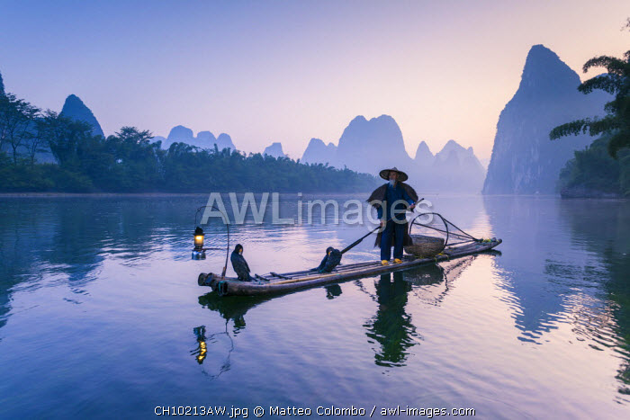 awl-images.com - China / China, Guanxi, Yangshuo. Old chinese fisherman at sunrise on the Li river, fishing with cormorants (MR)