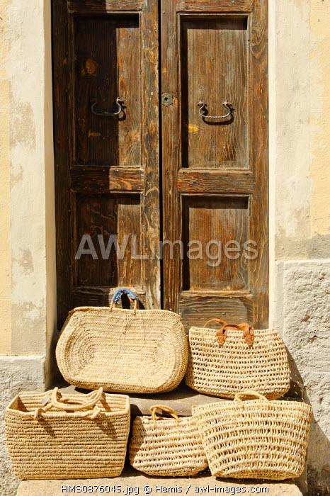Italy, Sardinia, Sassari Province, Gulf of Asinara, Castelsardo, raffia baskets on a staircase at the foot of a wooden door
