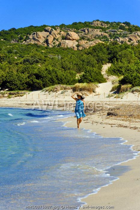 Italy, Sardinia, Olbia Tempio Province, the Emerald Coast (Costa Smeralda), Porto Cervo, Pevero beach, young woman in a blue sarong on a deserted beach walking on the sand along the shore