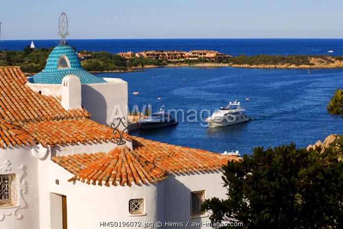 Italy, Sardinia, Olbia Tempio province, the Esmerald Coast (Costa Smeralda), Porto Cervo, Stella Maris church by architect Michele Busiri Vici, built in the 1960 's, and a yacht coming back to the marina