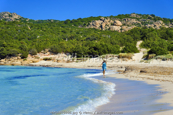 Italy, Sardinia, Olbia Tempio Province, the Emerald Coast (Costa Smeralda), Porto Cervo, Pevero beach, young woman in a blue sarong on a deserted beach walking on the sand along the shore