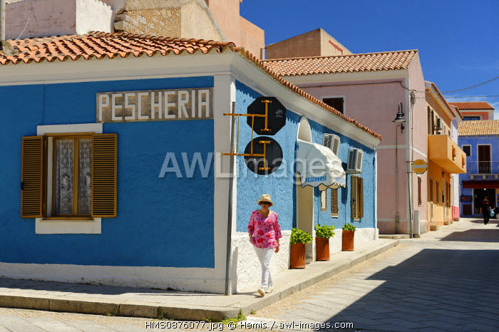 Italy, Sardinia, Olbia Tempio Province, Santa Teresa Gallura, Via Magnon, houses with pastel walls in the old village along the cobbled streets, young woman walking on a sidewalk