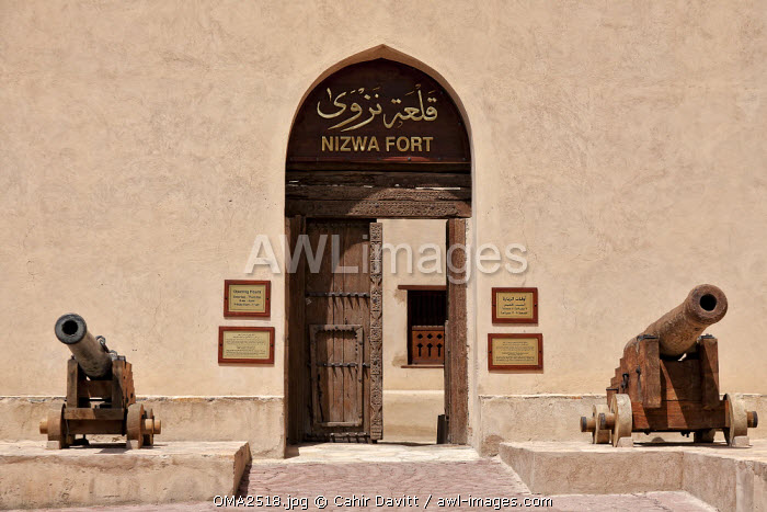 awl-images.com - Oman / General view of the entrance with 2 cannons either side of the ornate doorway to Nizwa Fort, Al Jinah, Nizwa, Ad Dakhiliyah Governorate, Oman.