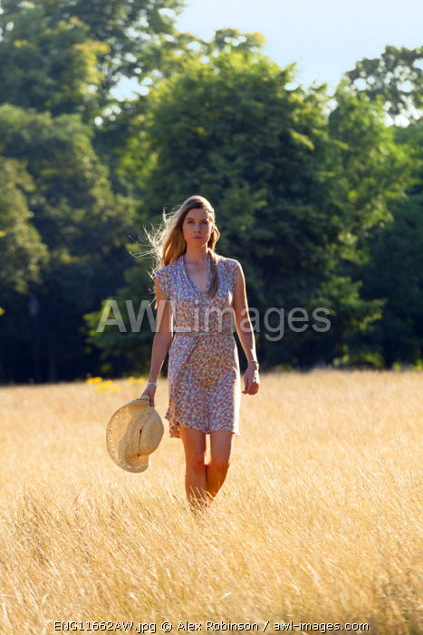 Europe, United Kingdom, England, an attractive young woman walking through a field in Summer MR