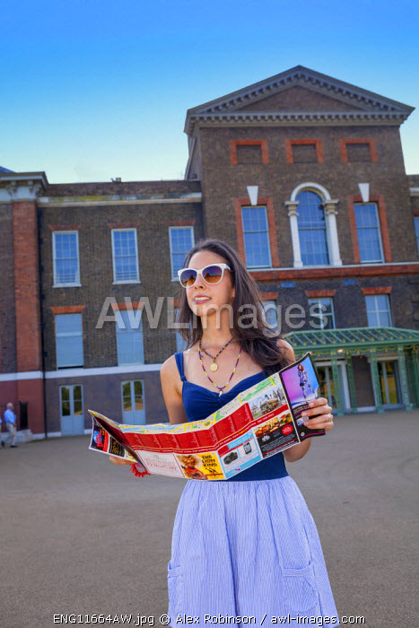 Europe, United Kingdom, England, London, Kensington, an attractive young woman with a touirst map in front of Kensington Palace MR