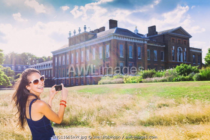 Europe, United Kingdom, England, London, Kensington, an attractive young woman taking a picture of Kensington Palace on her cell phone MR
