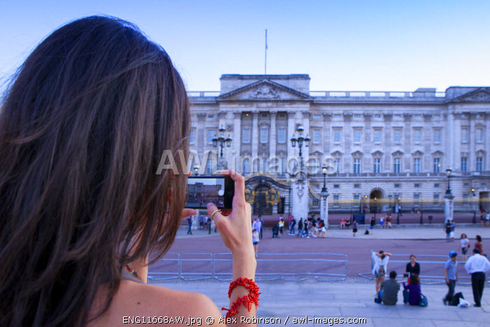 Europe, United Kingdom, England, London, Westminster, an attractive young woman taking a picture of Buckingham Palace on her cell phone MR