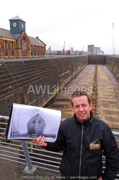 United Kingdom, Northern Ireland, Belfast, a Titanic tour guide holding a picture of the dock where Titanic was launched