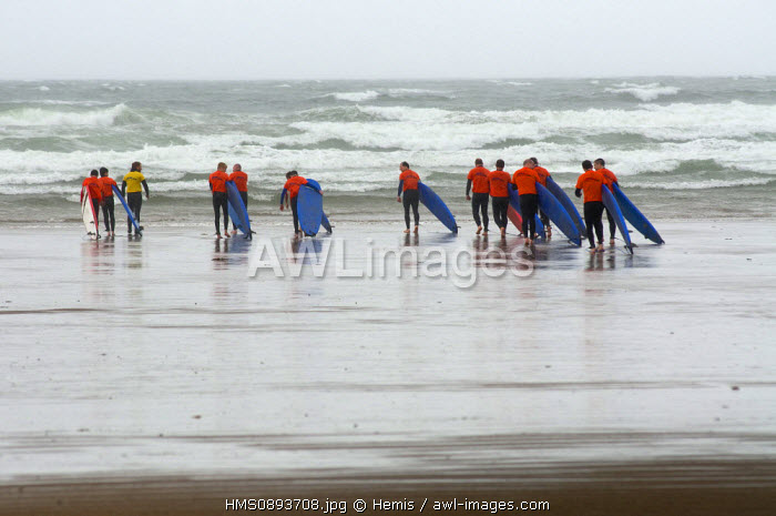 Ireland, County Kerry, Inch, surfers walking on the beach in bad weather