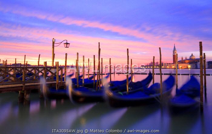 Italy, Venice. Gondolas moored on Riva degli Schiavoni at sunrise