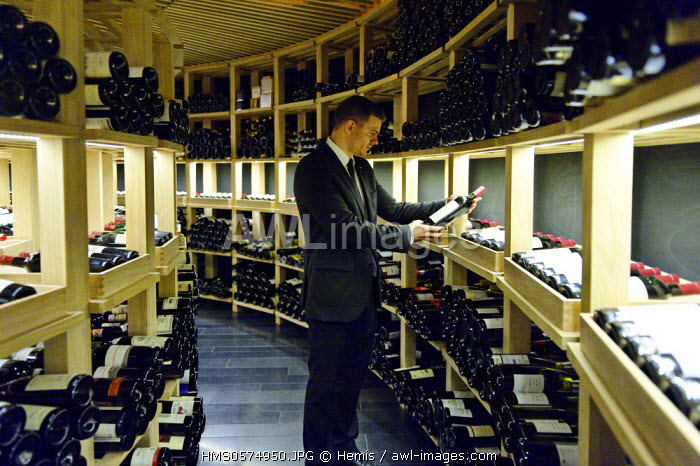 Spain, Extremadura, Caceres, San Mateo square, Parador of Tourism, sommelier choosing a bottle in the cellar of the hotel