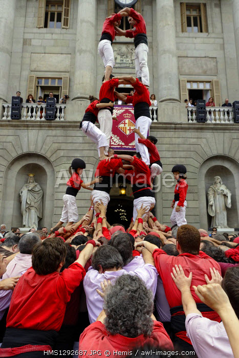 Spain, Catalonia, Barcelona, Castells human tower, living pyramid on top of which rises anxaneta, a child who salutes the crowd