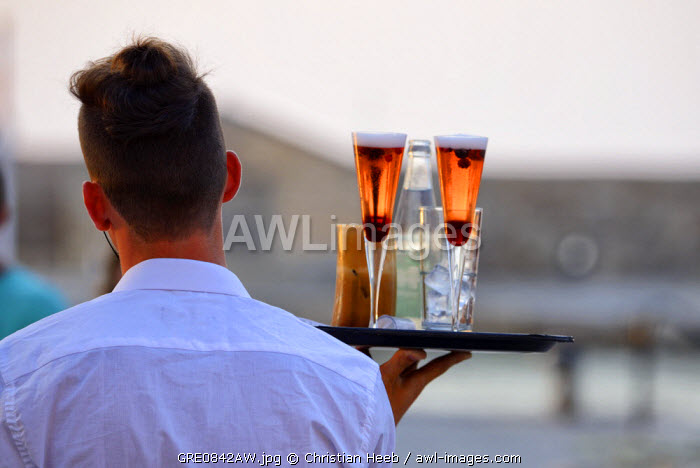 Waiter serving drinks in Chania, Crete, Greece, Europe