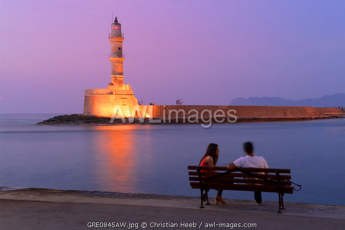 Couple sat watching the sunset at the waterfront in Charnia, Crete, Greece, Europe
