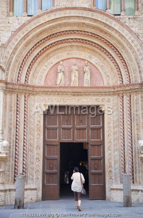 Woman entering Palazzo dei Priori, Perugia, Umbria, Italy
