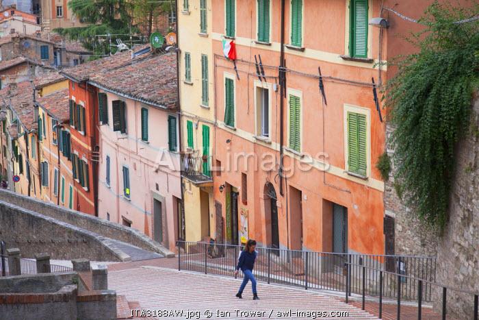 Woman walking along Via dei Priori, Perugia, Umbria, Italy