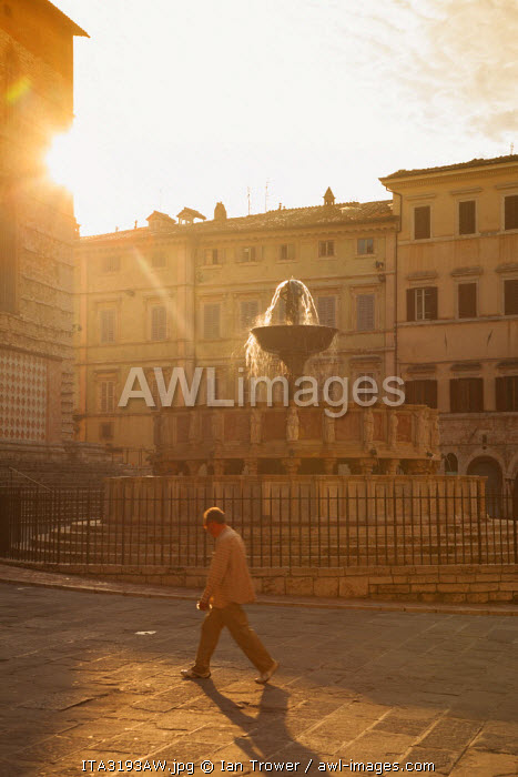 Man walking past Fontana Maggiore in Piazza IV Novembre at dawn Perugia, Umbria, Italy