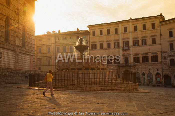 Woman walking past Fontana Maggiore in Piazza IV Novembre at dawn Perugia, Umbria, Italy