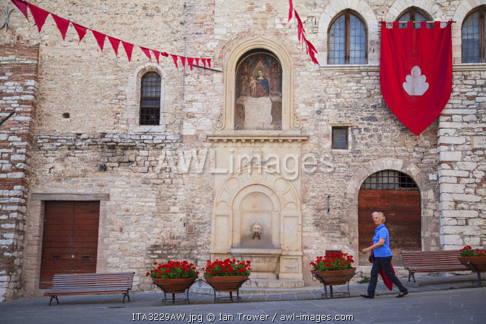 Woman walking past Church of the Trinity, Gubbio, Umbria, Italy