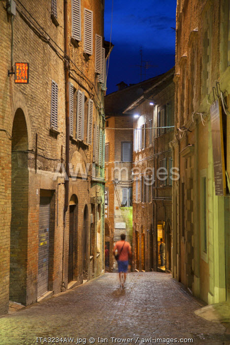 Man walking along street at dusk, Urbino (UNESCO World Heritage Site), Le Marche, Italy