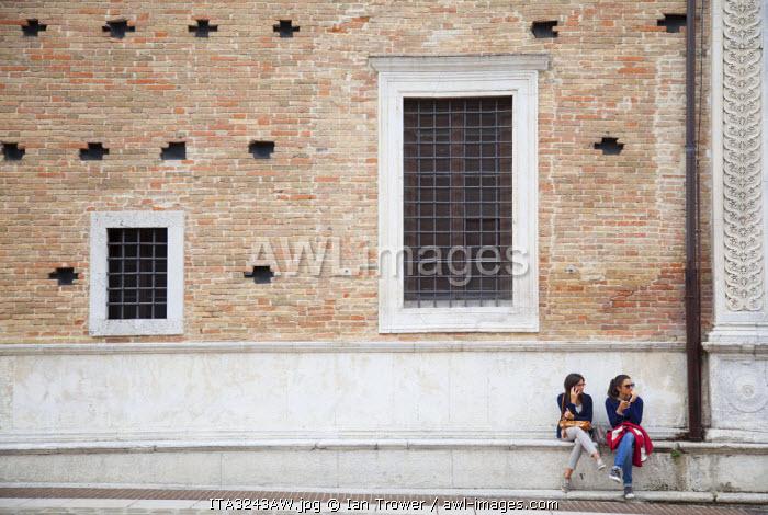Women sitting outside Palazzo Ducale, Urbino (UNESCO World Heritage Site), Le Marche, Italy