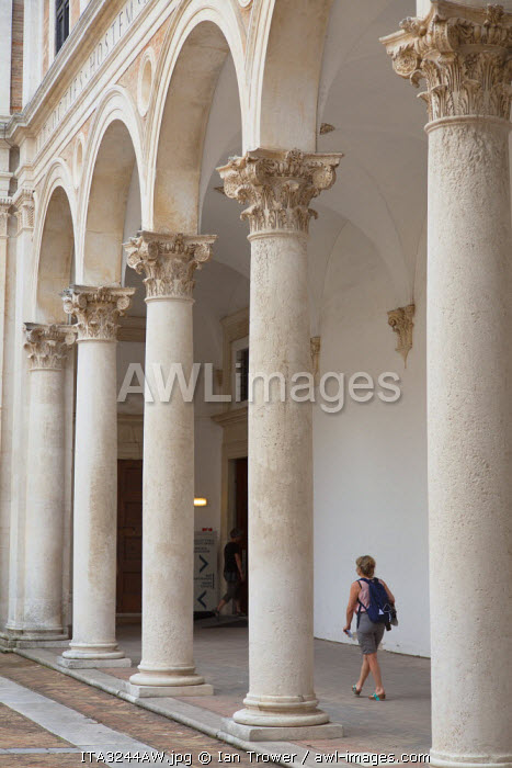 Woman walking in courtyard of Palazzo Ducale, Urbino (UNESCO World Heritage Site), Le Marche, Italy