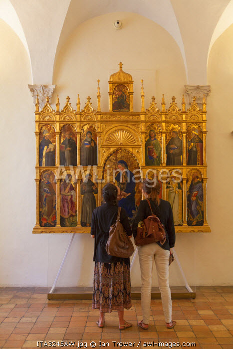 Women looking at religious icon inside Palazzo Ducale, Urbino (UNESCO World Heritage Site), Le Marche, Italy