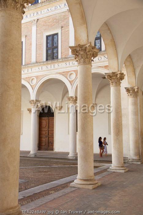 Women walking in courtyard of Palazzo Ducale, Urbino (UNESCO World Heritage Site), Le Marche, Italy