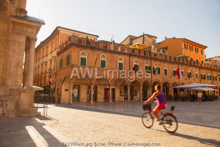 Woman cycling through Piazza del Popolo, Ascoli Piceno, Le Marche, Italy