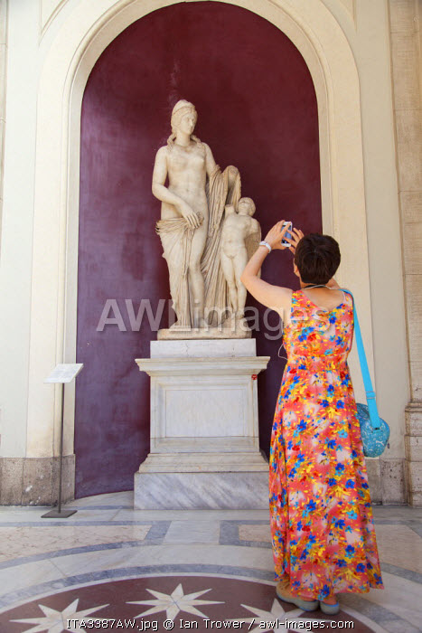 Woman taking photo of statue inside Vatican Museum (UNESCO World Heritage Site), Vatican City, Rome, Italy