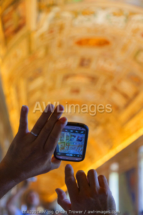 Person takign photo on phone of Gallery of Maps inside Vatican Museum (UNESCO World Heritage Site), Vatican City, Rome, Italy