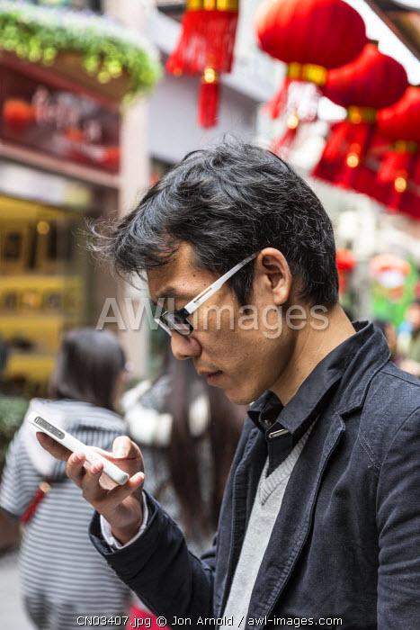 Young man texting on his smartphoneTianzifang, French Concession, Shanghai, China