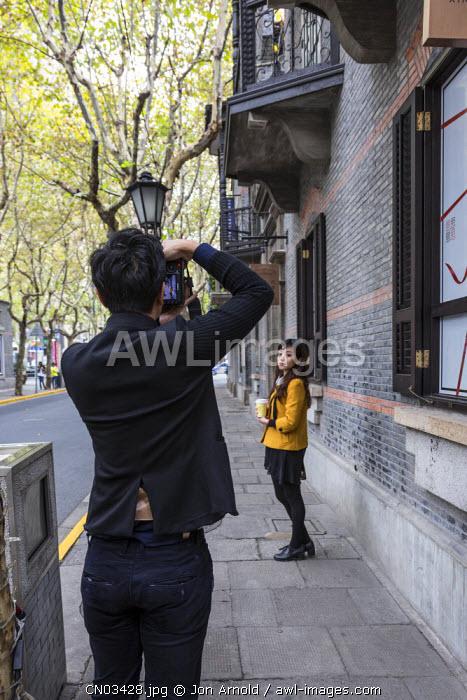 Man taking photo of a woman, Xintiandi, Shanghai, China