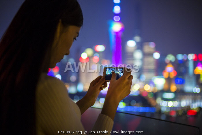 Woman taking photos with smartphone infornt of the Pudong skyline, Shanghai, China (MR)
