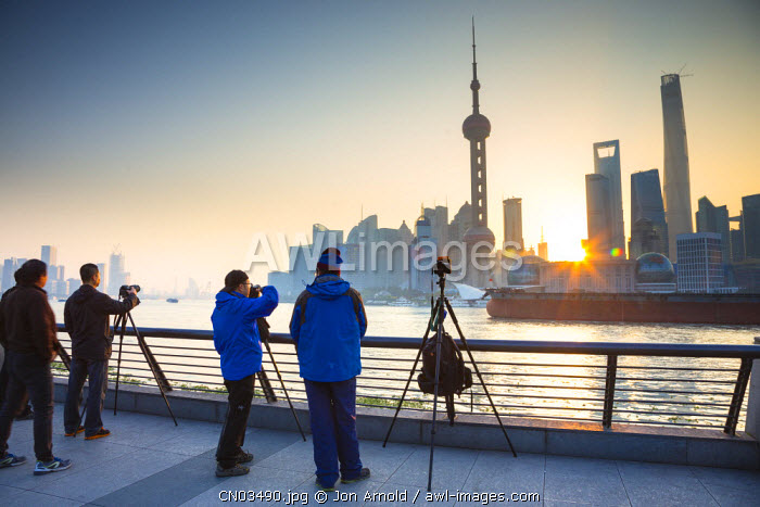 Amateur photographers taking pictures of the Pudong skyline across the Huangpu river, The Bund, Shanghai, China