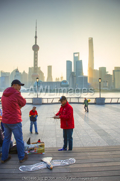 Kite flyers on the Bund with the Pudong skyline across the Huangpu river, Shanghai, China
