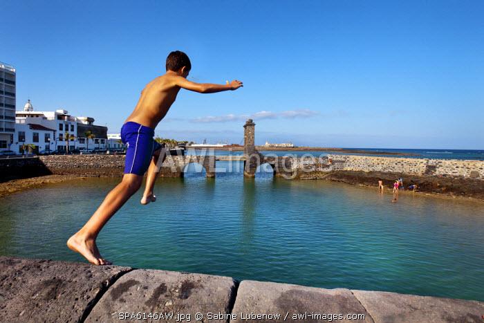 Boy jumping in the water, Puente de las Bolas, Arrecife, Lanzarote, Canary Islands, Spain