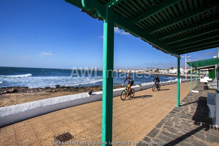 Cyclists on the promenade, Playa Honda, Lanzarote, Canary Islands, Spain