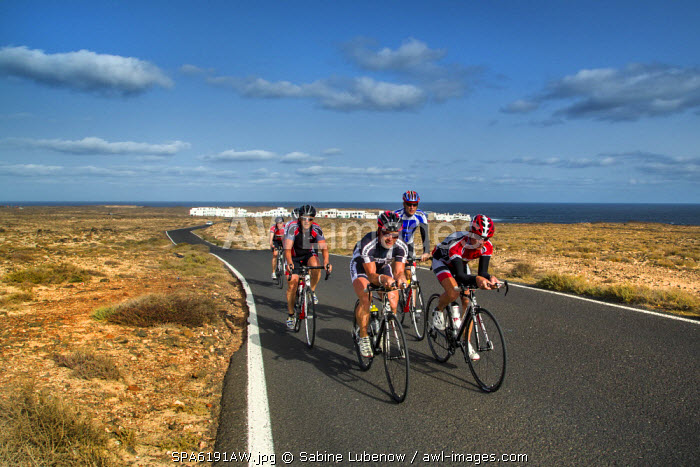 Cyclists above fishing village Caletta de Caballo, La Santa, Lanzarote, Canary Islands, Spain